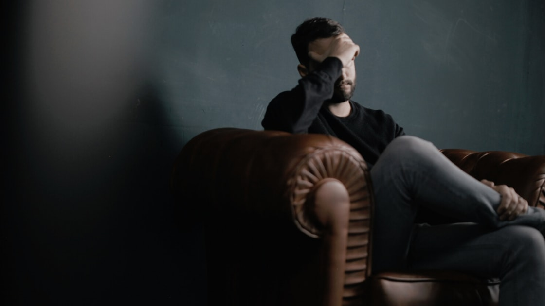 Chiropractic Care for Tension Headaches - man holding his head in pain