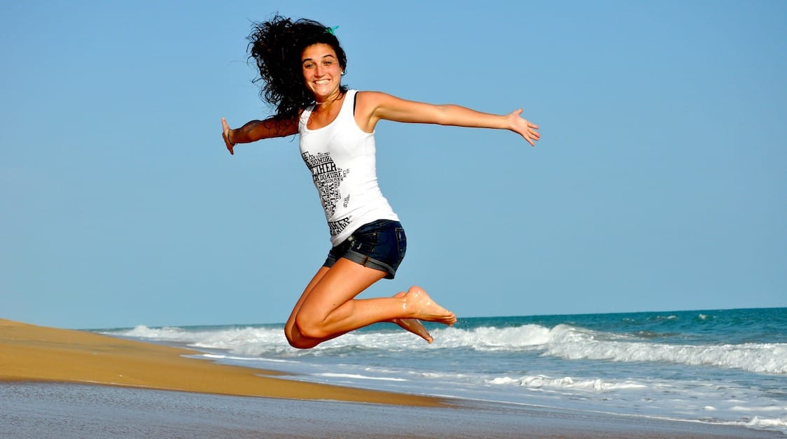 Girl jumping on beach feeling good between massages
