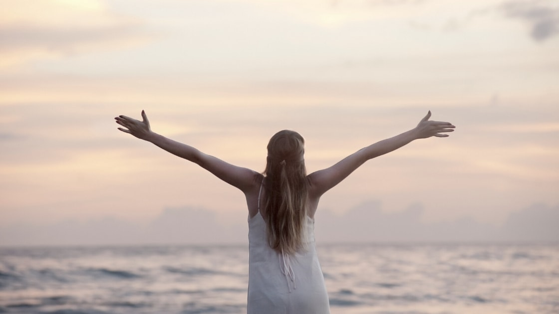 Turning stress into your ally - girl with arms out wide in front of sunset