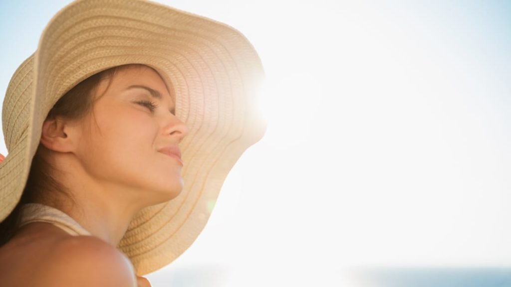 Sunshine and Coronavirus - woman with hat in sun