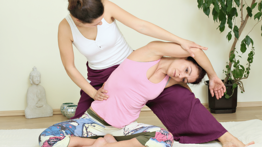 Girl doing massage and yoga assisted by instructor
