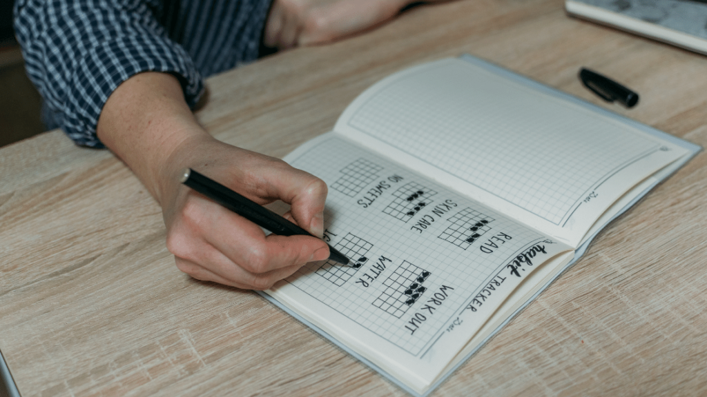 Person writing in fitness journal