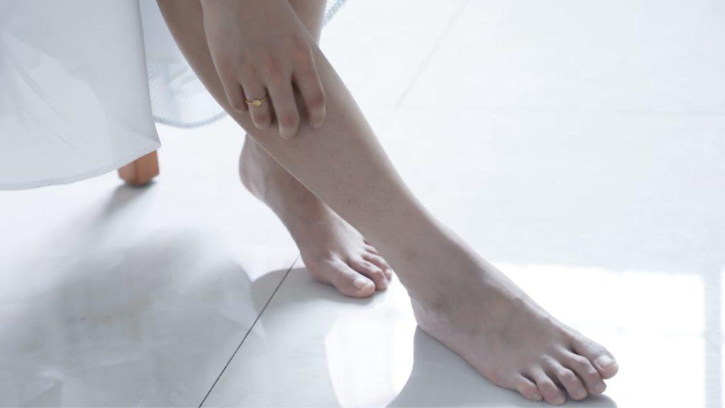 Woman touching fascia on legs