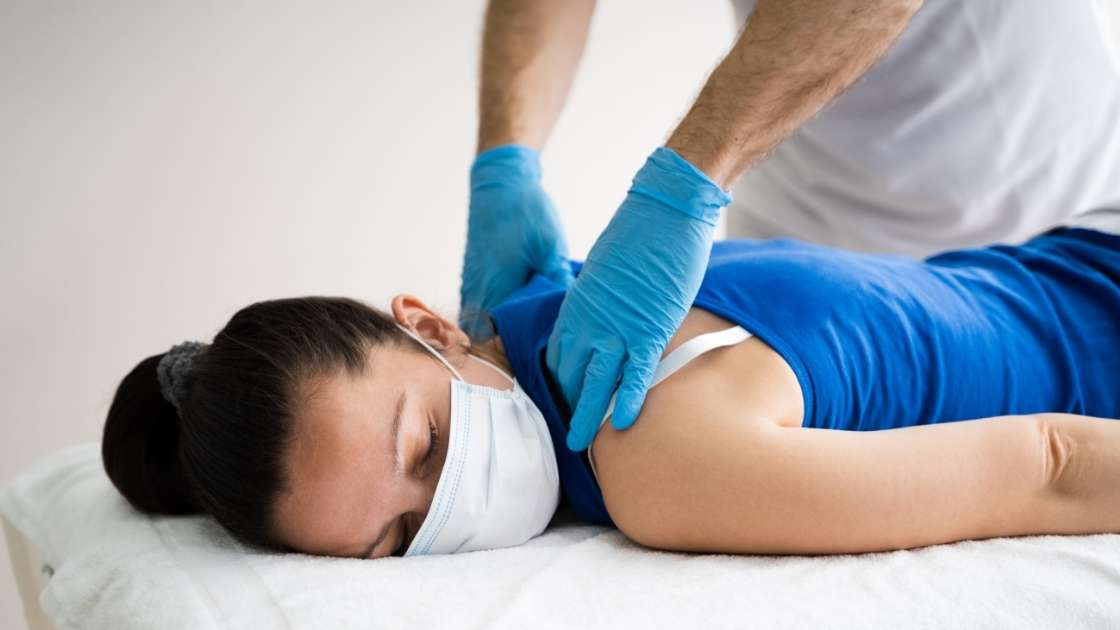 person getting a neck and back massage with a face mask on