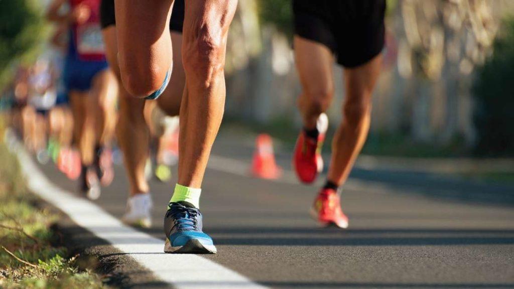 people running a marathon feet only