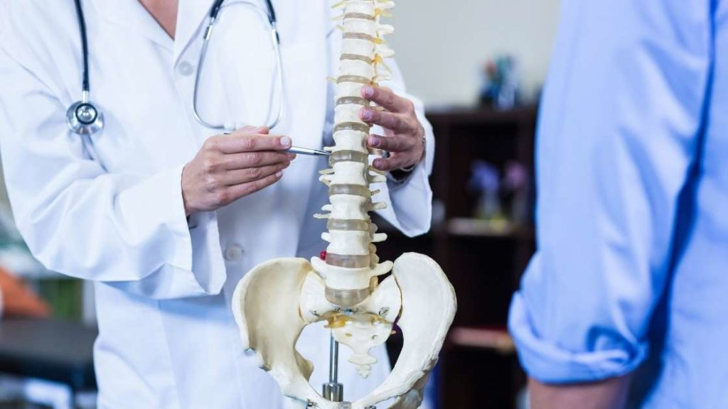 chiropractor pointing to a spinal subluxation on a skeleton of the spine