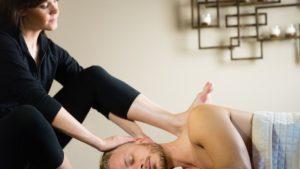 female massage therapist giving ashiatsu massage on guy's traps
