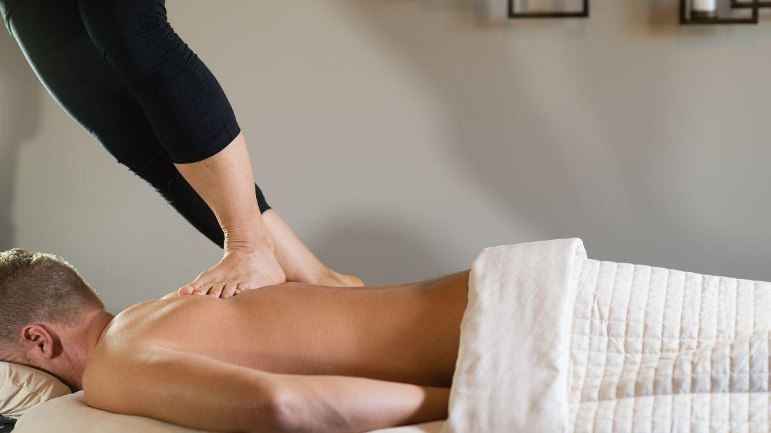 woman giving ashiatsu massage on guys back