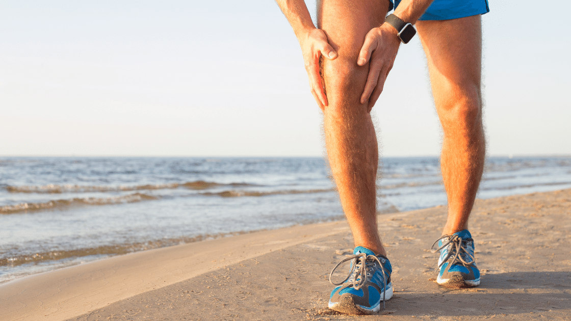 person grabbing knee in pain on the beach with an acl injury