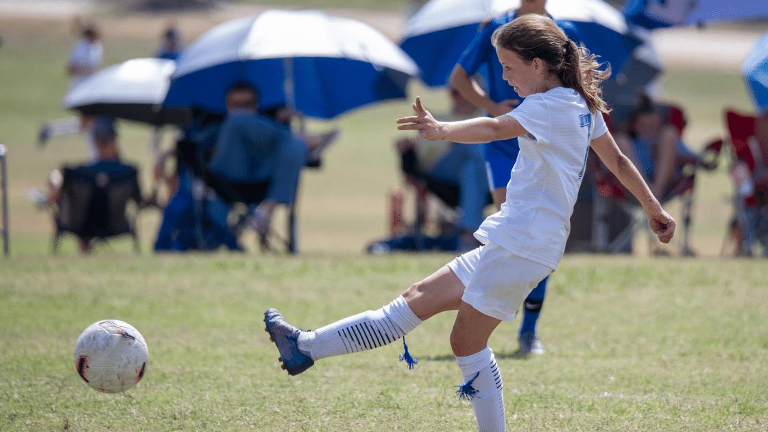 girl kicking a soccer ball