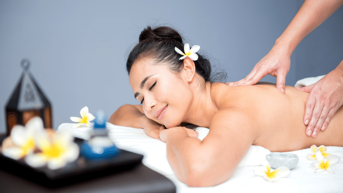 girl smiling and covered in flowers as she gets a back massage
