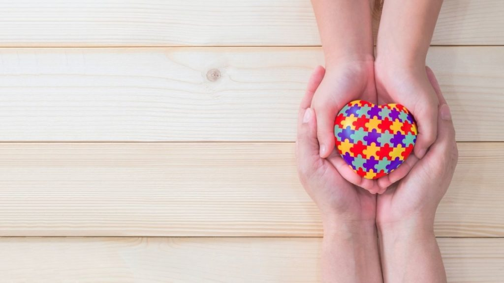 Two hands holding a colorful heart