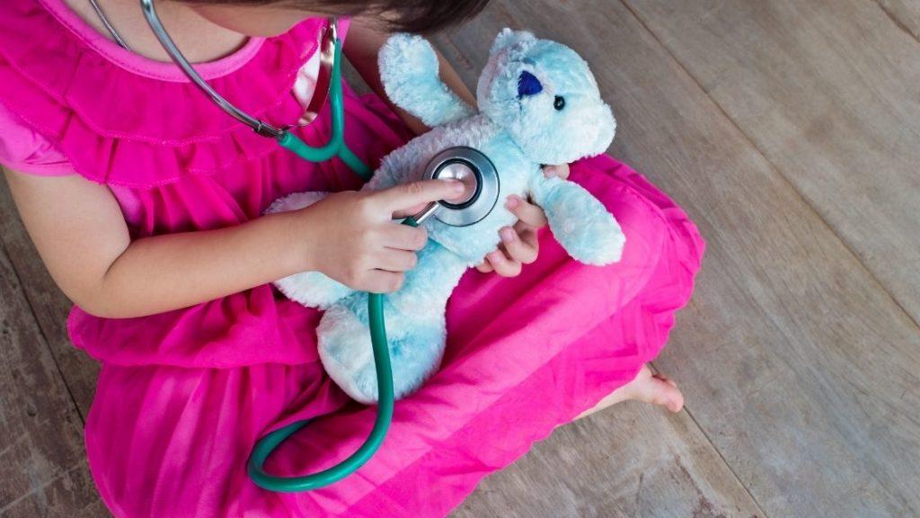 kid holding stethoscope to stuffed bear